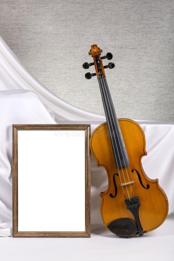 Marco de la foto para su maqueta en la tabla con el violín imagen de archivo libre de regalías
