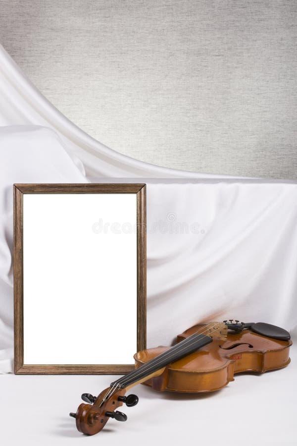 Marco de la foto para su maqueta en la tabla con el violín imagenes de archivo