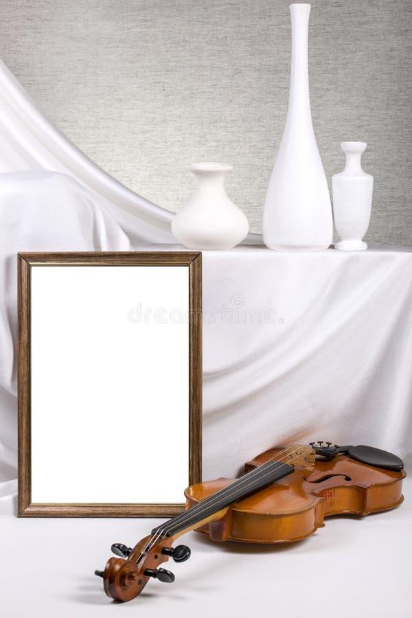 Marco de la foto para su maqueta en la tabla con el violín y los floreros imagen de archivo libre de regalías