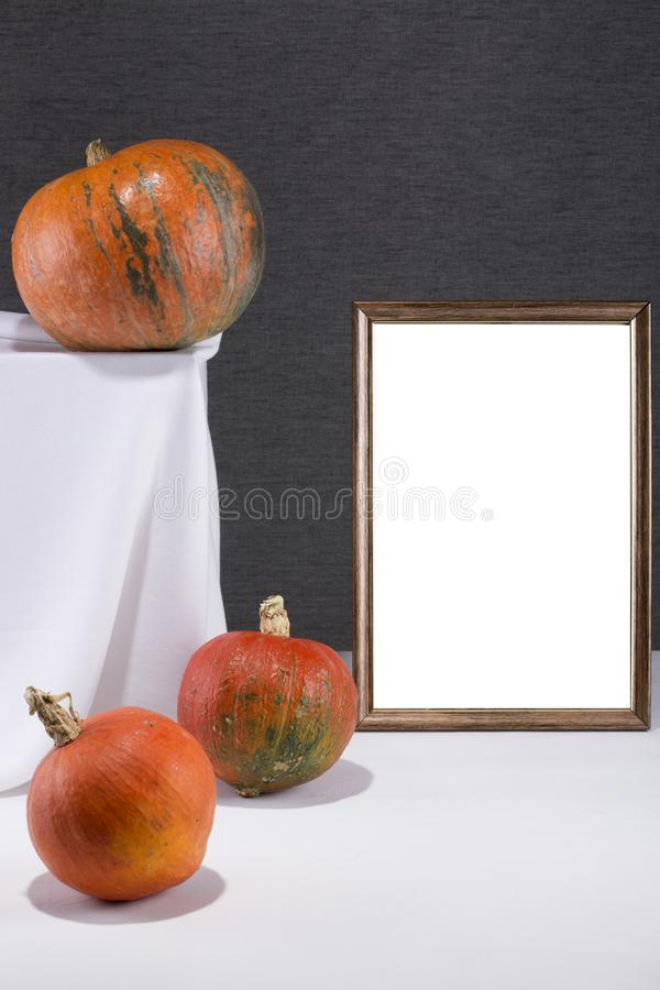 Marco de la foto para su maqueta en la tabla con las calabazas imagen de archivo