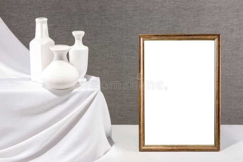 Marco de la foto para su maqueta en la tabla con los floreros fotografía de archivo