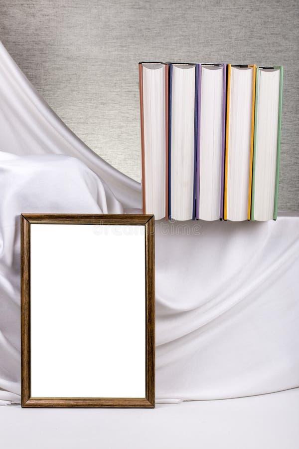 Marco de la foto para su maqueta en la tabla con los libros fotos de archivo libres de regalías