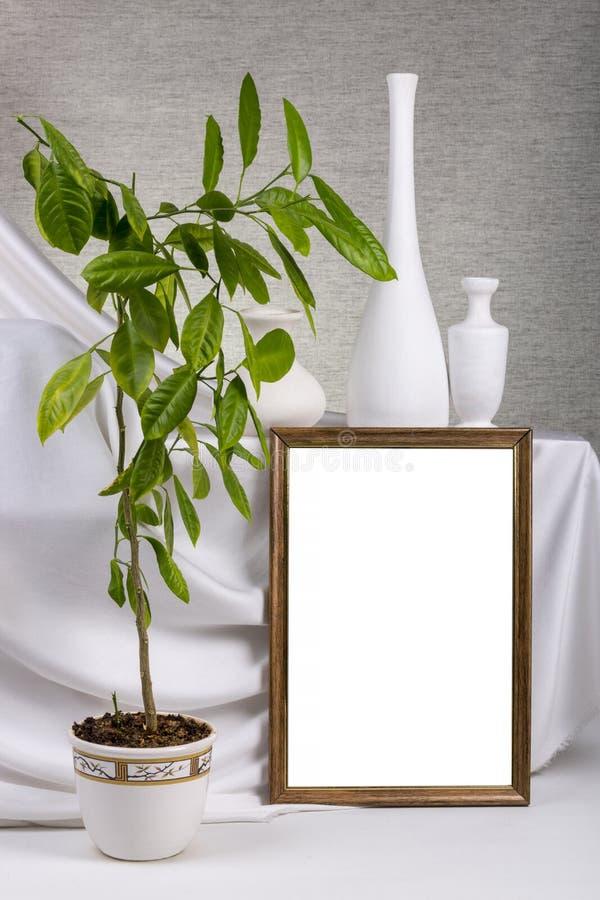 Marco de la foto para su maqueta en la tabla con la planta interior fotografía de archivo