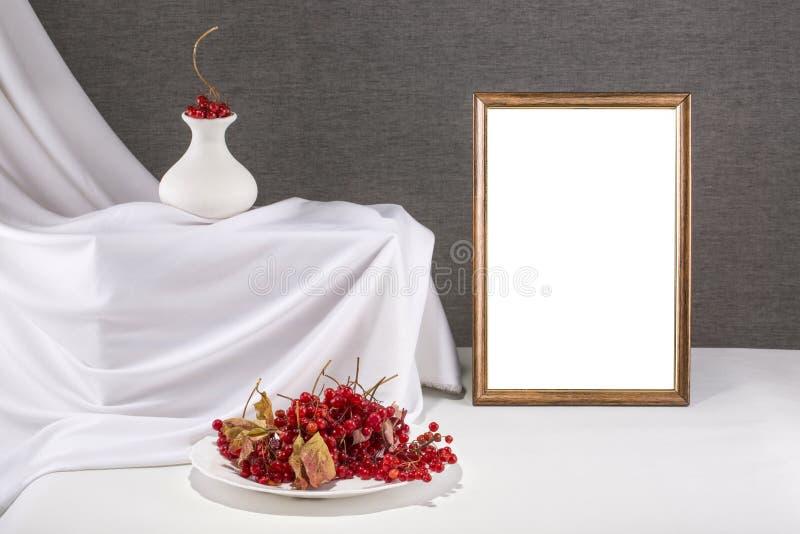 Marco de la foto para su maqueta en una tabla con rojo del viburnum fotografía de archivo libre de regalías