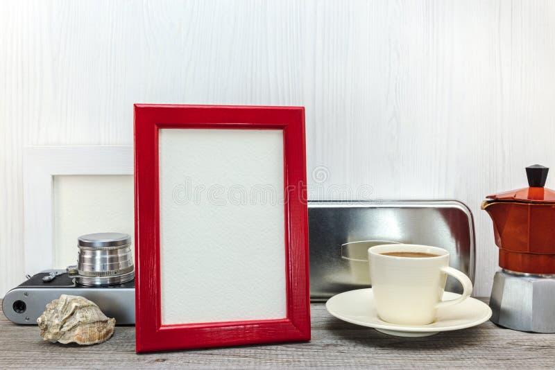 Marco de la foto y pote rojos del café con la taza en el backgrou de madera blanco foto de archivo