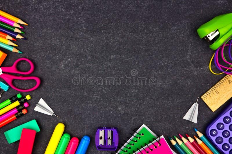 Marco de la frontera de las fuentes de escuela, opinión superior sobre un fondo de la pizarra con el espacio de la copia De nuevo fotografía de archivo libre de regalías