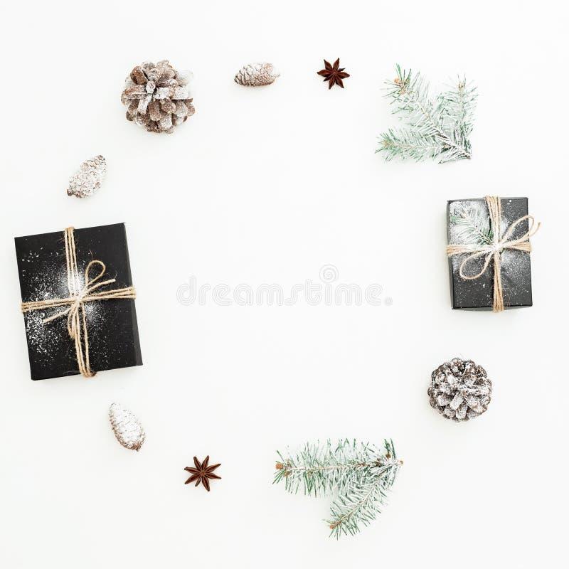 Marco de la Navidad hecho de la caja de regalo, de ramas del abeto y de conos negros elegantes del pino en el fondo blanco Concep fotos de archivo