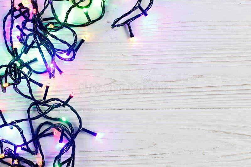 Marco de la Navidad de las luces de la guirnalda frontera elegante colorida en wh imagen de archivo