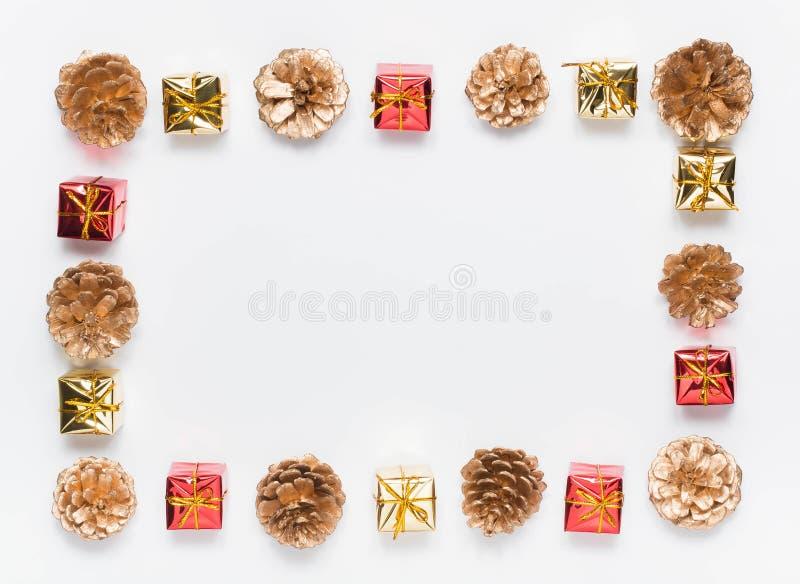 Marco de la Navidad, modelo de los conos del pino y pequeñas cajas de regalo, en un fondo blanco imagen de archivo