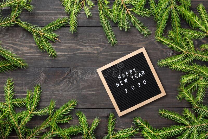 Marco de la Navidad o del Año Nuevo para su proyecto Palabras de la Feliz Año Nuevo 2020 en un tablero de la letra con las ramas  fotografía de archivo libre de regalías