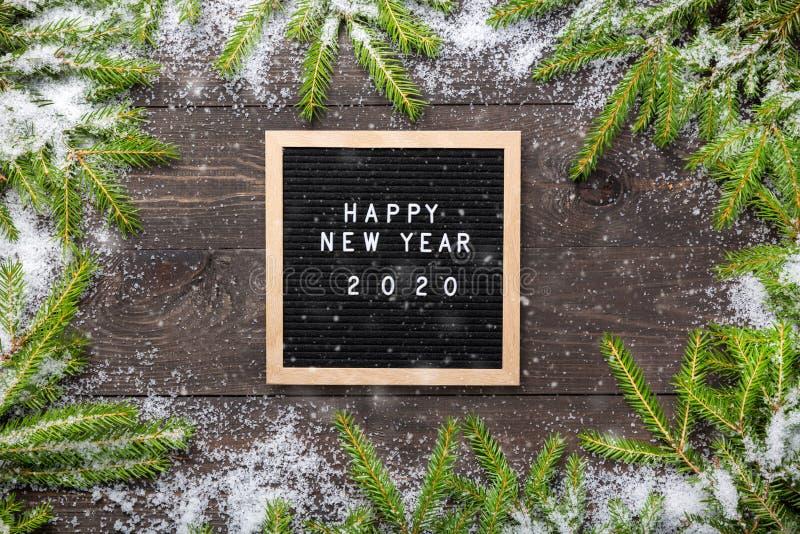 Marco de la Navidad o del Año Nuevo para su proyecto Palabras de la Feliz Año Nuevo 2020 en un tablero de la letra con las ramas  imagen de archivo libre de regalías