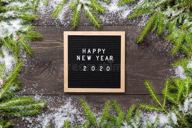 Marco de la Navidad o del Año Nuevo para su proyecto Palabras de la Feliz Año Nuevo 2020 en un tablero de la letra con las ramas  imagen de archivo