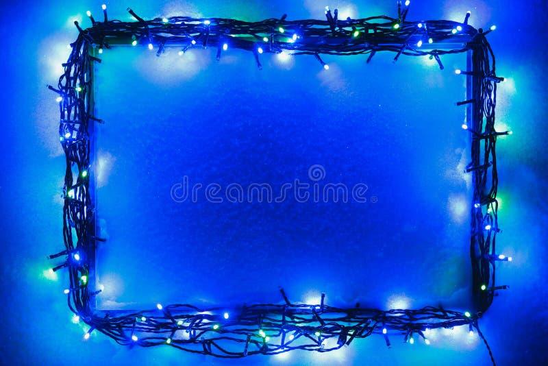 Marco de las luces de la Navidad en fondo de la nieve fotos de archivo