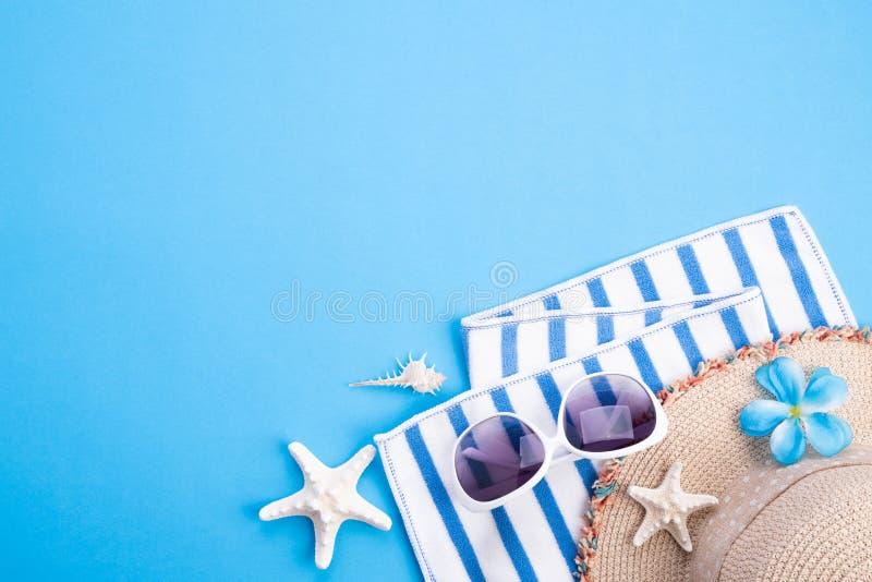 Marco de los accesorios de la playa, gafas de sol, estrellas de mar, sombrero de la playa y cáscara del mar en el fondo azul par fotografía de archivo