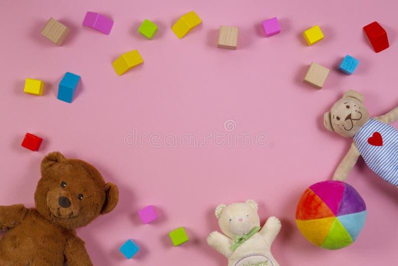 Marco de los juguetes de los niños del bebé con el oso de peluche, bloques de madera coloridos en fondo rosado Visión superior foto de archivo