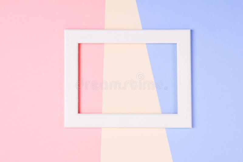 Marco de madera blanco sobre fondo de papel colorido en colores pastel fotos de archivo