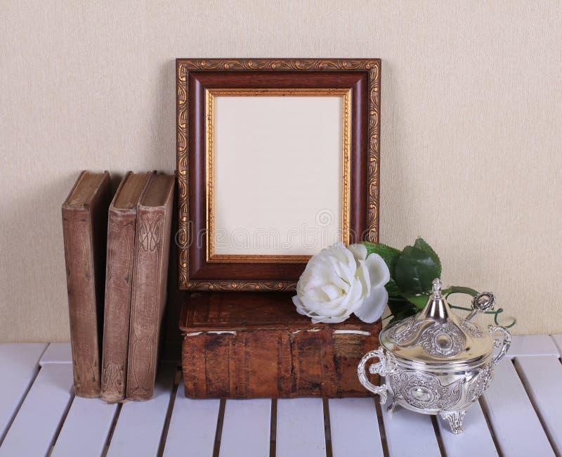 Marco de madera con los libros viejos en la tabla fotos de archivo