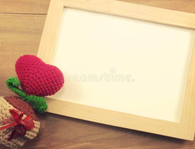 Marco de madera de la foto y día de tarjetas del día de San Valentín rojo del corazón en fondo de madera imagenes de archivo