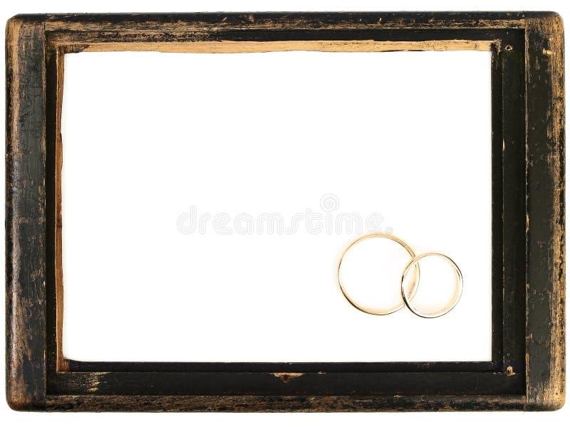 Marco de madera de la vendimia y anillos de bodas foto de archivo libre de regalías