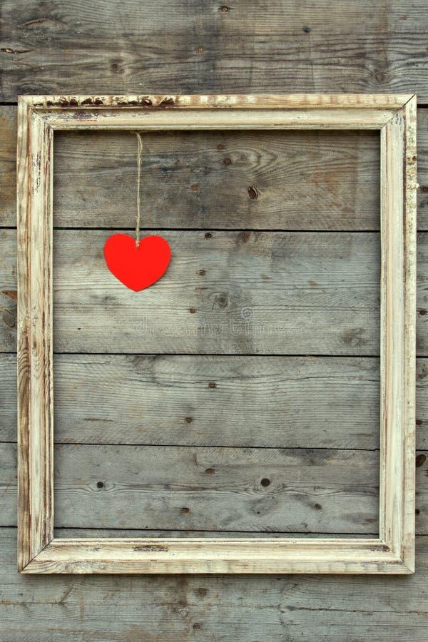 Marco de madera del vintage con el corazón rojo en un fondo del grunge foto de archivo libre de regalías