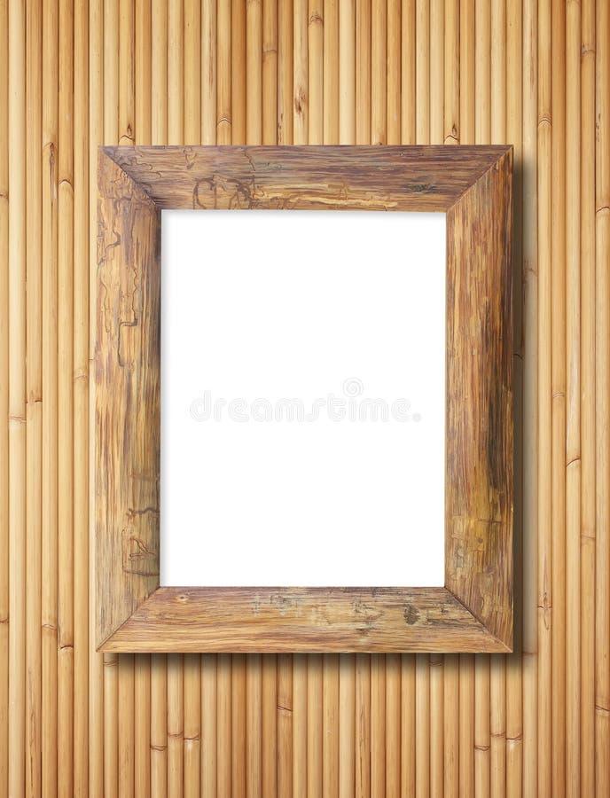 Marco de madera en blanco en la pared de bambú imagenes de archivo