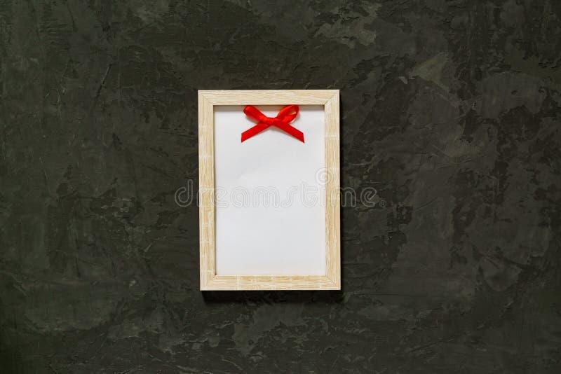 Marco de madera de la foto con el lazo de satén rojo en fondo negro Maqueta fotos de archivo