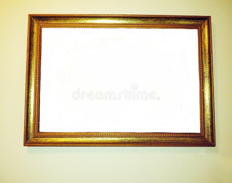 Marco de madera de oro vacío en una pared imagenes de archivo