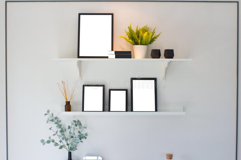 Marco de madera y árbol negros en blanco en estante sobre el cemento blanco wal imagenes de archivo