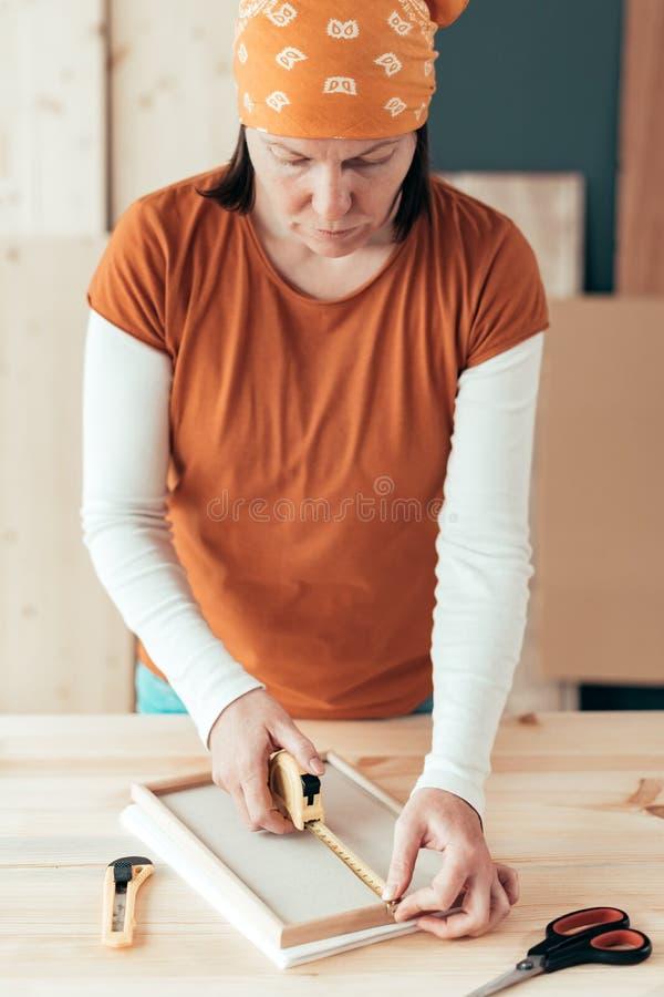 Marco de medición de la cinta femenina del carpintero en taller imagen de archivo libre de regalías