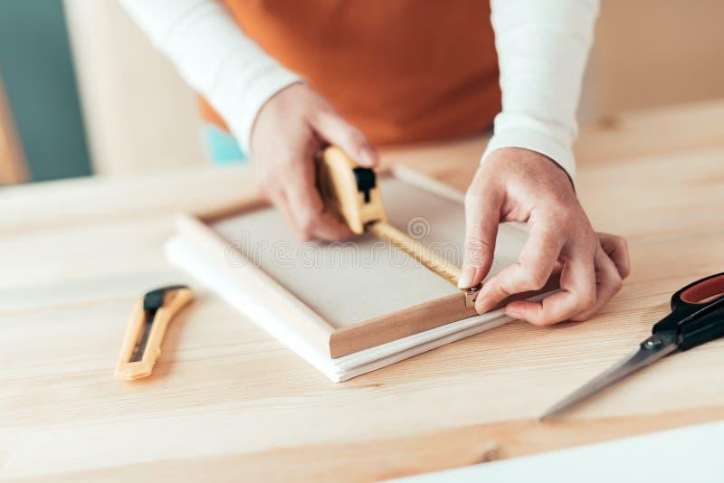 Marco de medición de la cinta femenina del carpintero en taller fotos de archivo libres de regalías
