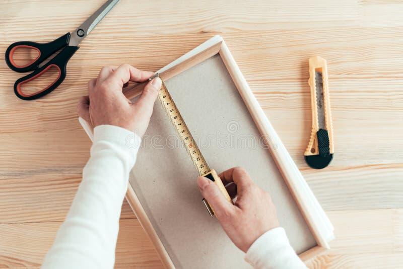 Marco de medición de la cinta femenina del carpintero en taller fotos de archivo