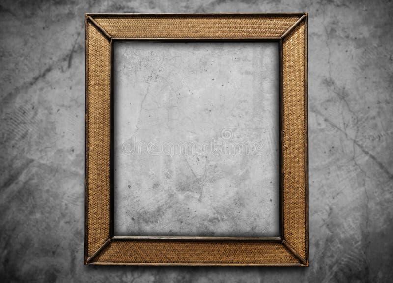 Marco de mimbre de la rota, en fondo del muro de cemento fotografía de archivo
