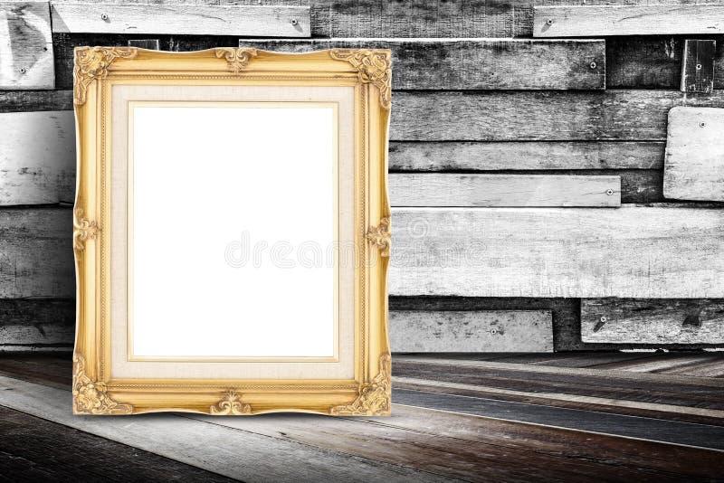 Marco de oro en blanco de la foto del vintage que se inclina en la pared de madera del tablón y imagenes de archivo