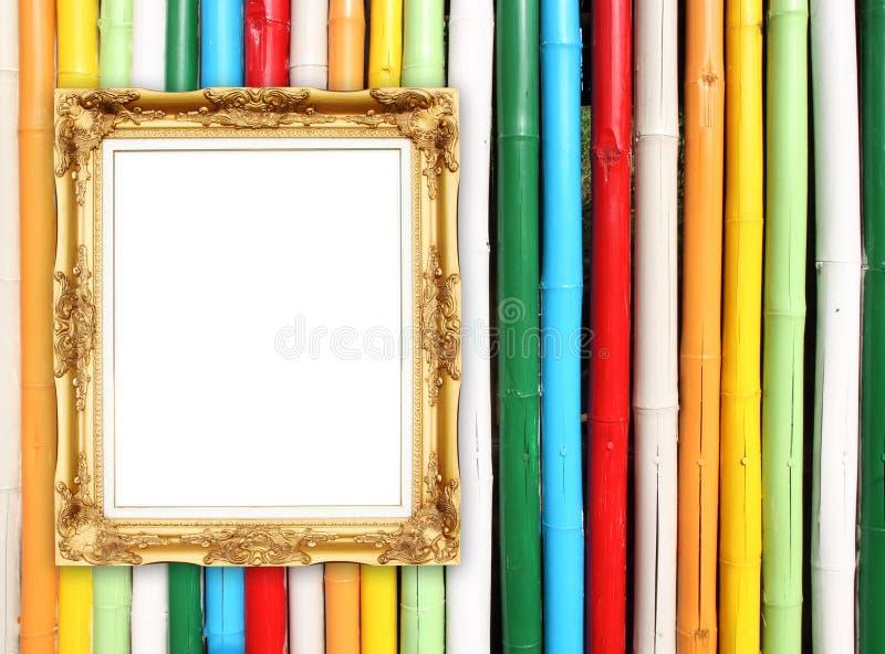 Marco de oro en blanco en la pared de bambú colorida imágenes de archivo libres de regalías
