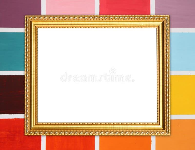 Marco de oro en blanco en la pared de madera colorida foto de archivo libre de regalías