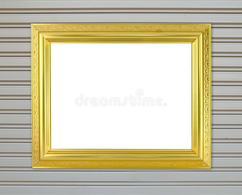 Marco de oro en blanco en la pared del metal imagenes de archivo