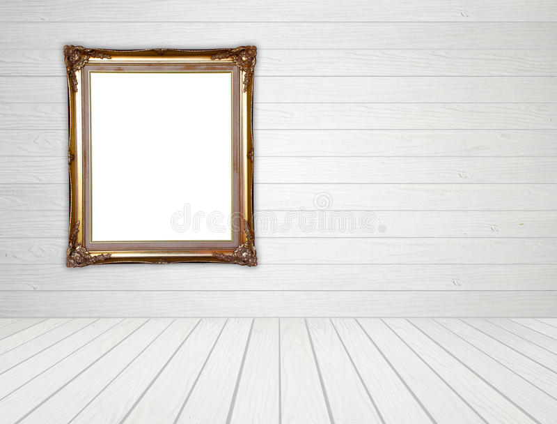 Marco de oro en blanco en sitio con el piso de madera blanco de la pared y de madera fotografía de archivo