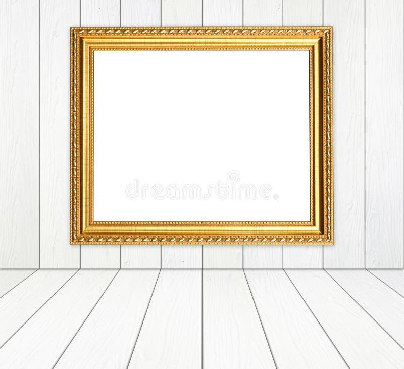Marco de oro en blanco en sitio con el piso de madera blanco de la pared y de madera fotos de archivo libres de regalías