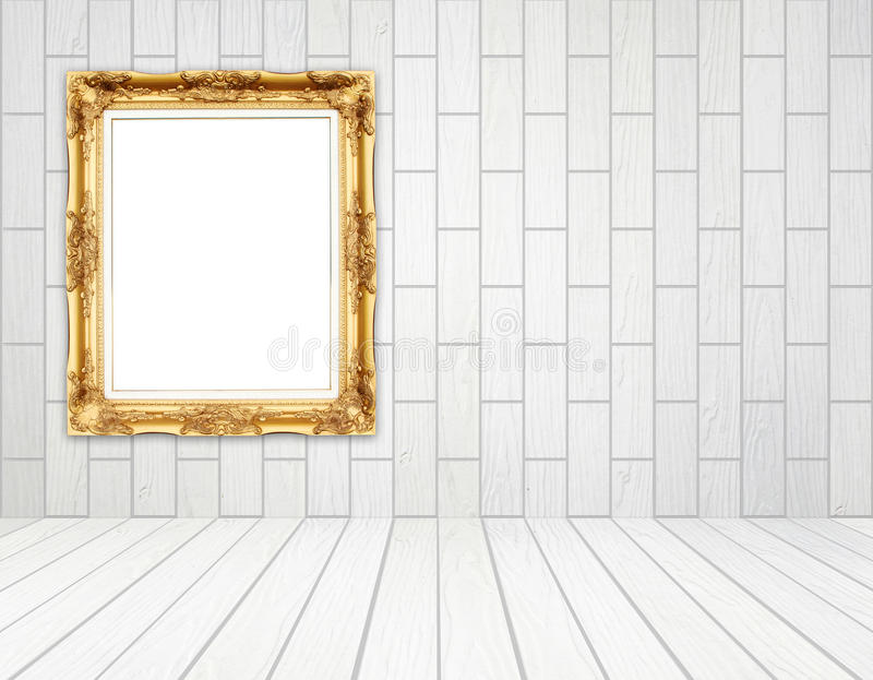 Marco de oro en blanco en sitio con la pared de madera blanca (estilo del bloque) foto de archivo