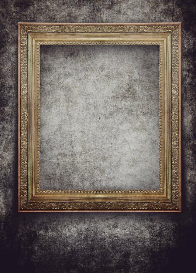 Marco de oro en la pared del negro del grunge foto de archivo