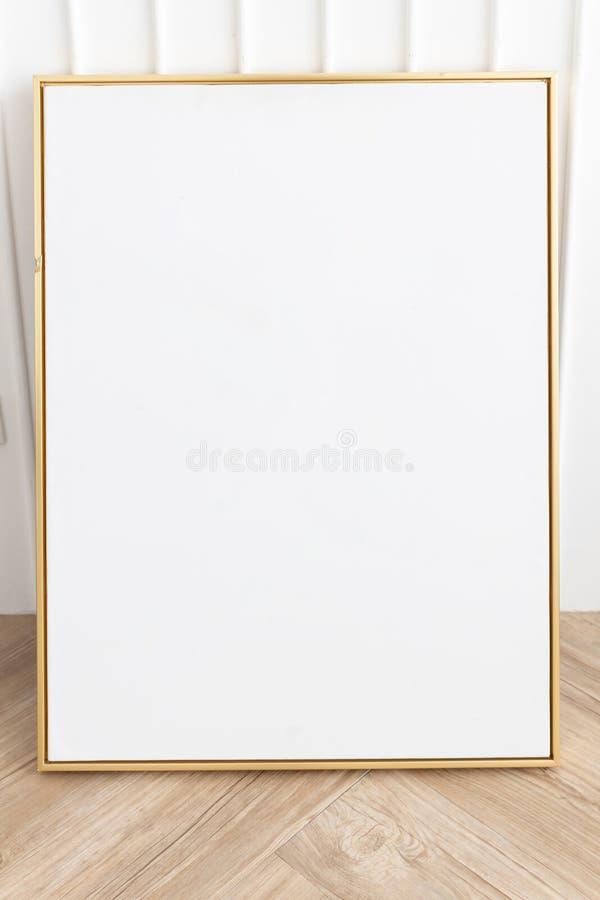 Marco de oro vacío con la pared blanca en piso de madera fotos de archivo libres de regalías