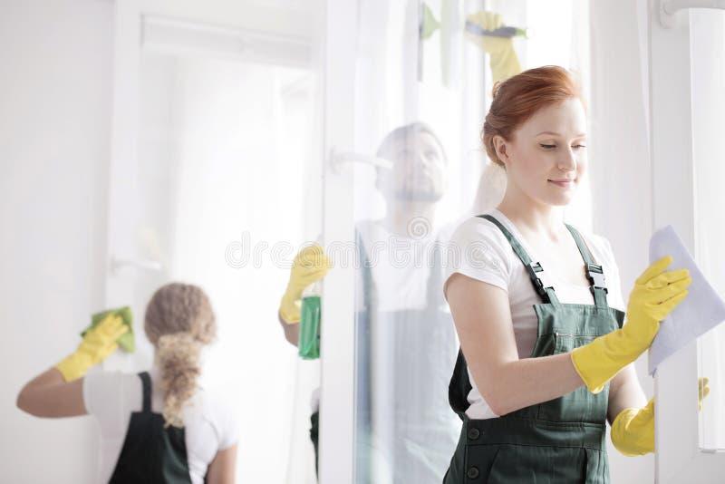 Marco de ventana de la limpieza de la mujer fotografía de archivo libre de regalías