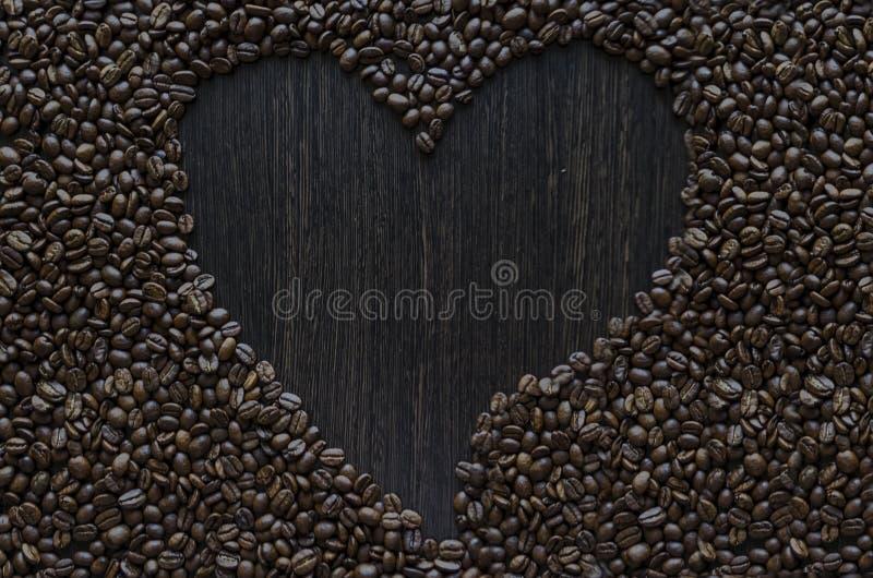 Marco del café del corazón hecho de los granos de café en fondo oscuro de madera Copie el espacio imágenes de archivo libres de regalías