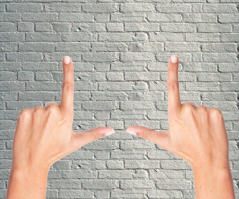 Marco del finger sobre la pared de ladrillo gris foto de archivo libre de regalías