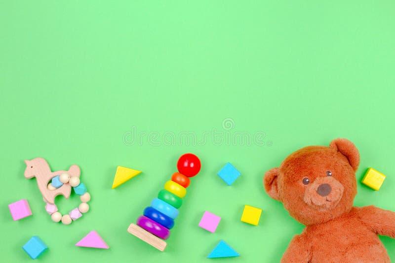 Marco del fondo de los juguetes de los niños con el oso de peluche y bloques coloridos en fondo verde imagen de archivo