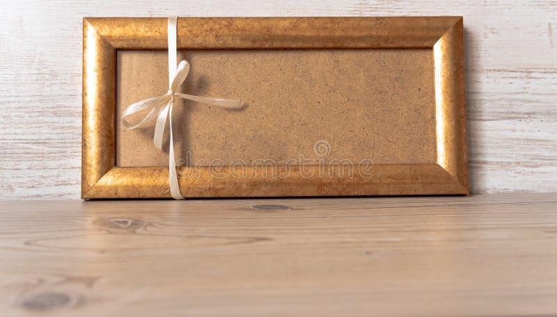 Marco del oro con un arco blanco en el fondo de madera gris imagen de archivo libre de regalías