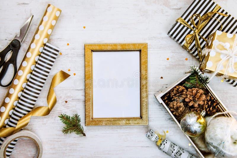 Marco del ptoto, cajas de regalo de oro, un cajón por completo de conos del pino y de juguetes de la Navidad y de materiales de e imagen de archivo