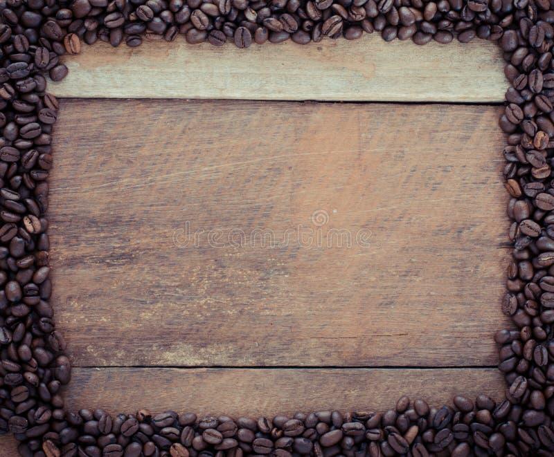 Marco del rectángulo hecho de los granos de café en el fondo de madera foto de archivo