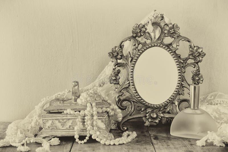 Marco en blanco antiguo del estilo del victorian, botella de perfume y perlas blancas en la tabla de madera Foto blanco y negro d foto de archivo libre de regalías