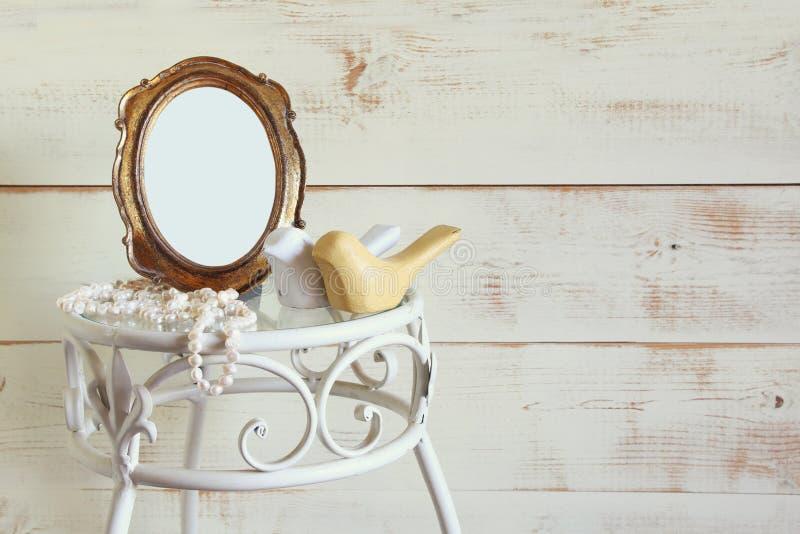 Marco en blanco antiguo del estilo del vintage, perlas blancas y pares de pájaros de madera en la tabla elegante la plantilla, al foto de archivo
